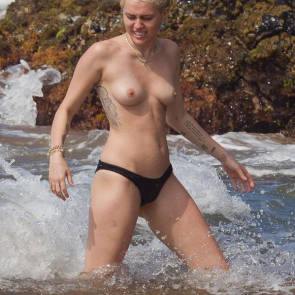 Miley Cyrus topless spalshing by waves