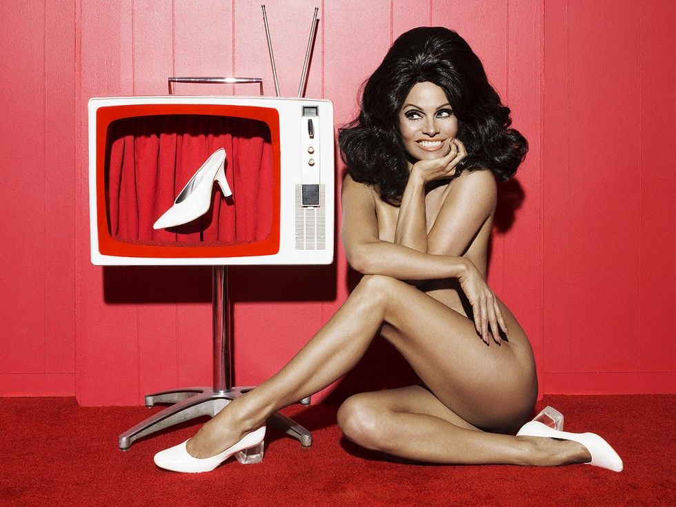 Pamela Anderson sitting by TV naked