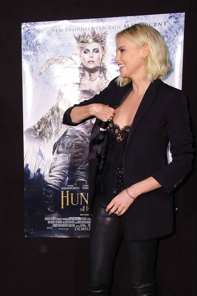 charlize theron trying to fix her top while nipple sliping out