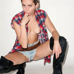 Miley Cyrus crouched sucking fingers and showing naked tits
