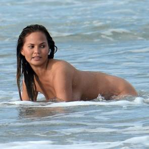 Chrissy Teigen in water kneeling
