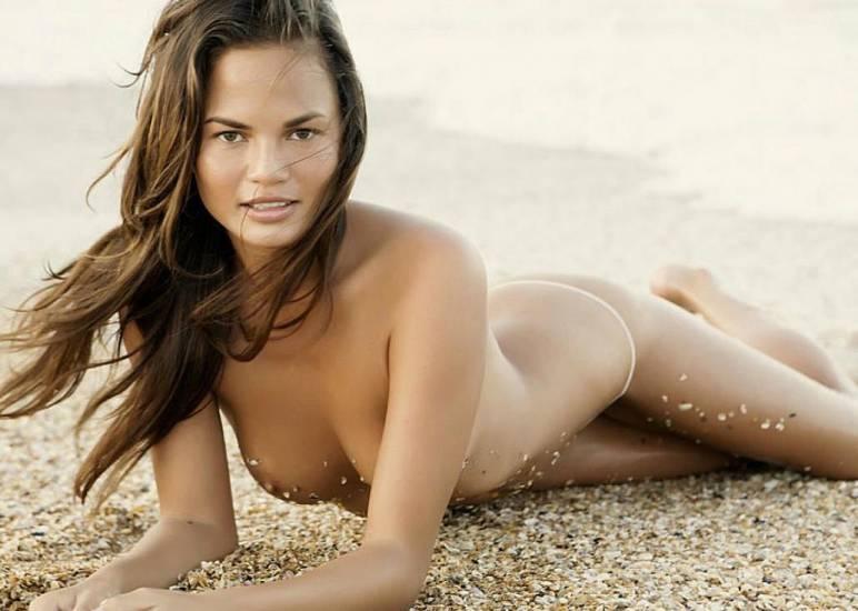 Chrissy Teigen lying on the sand naked