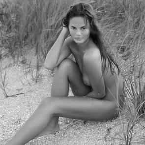 Chrissy Teigen sitting on the sand