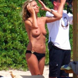 Heidi Klum adjusting her hair and with no top on
