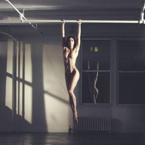Hilary Rhoda nude hanging on bar