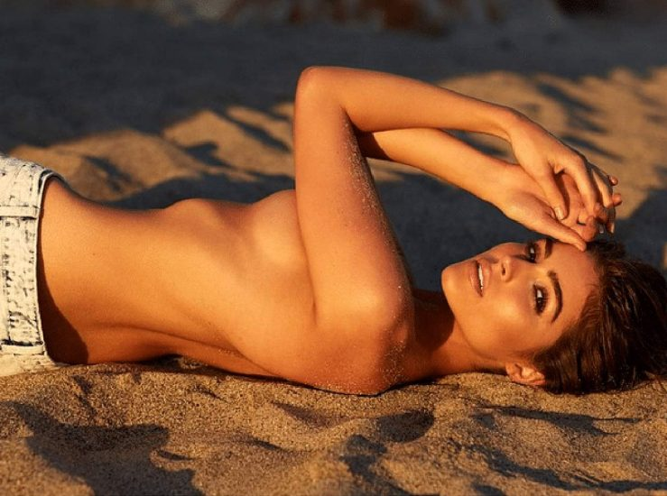 Olivia Culpo laying on the sand